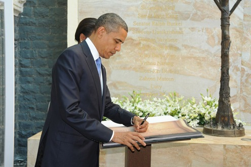 The President Barack Obama signing the visitor's book after paying tributes, at the memorial for victims of 26/11 sea-borne terror attacks, at Hotel Taj Mahal, in Mumbai.